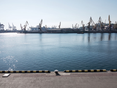 Odessa, Ukraine - August 15, 2016: Container cranes in cargo port terminal, cargo cranes without job in an empty harbor port. A crisis. Defaulted paralyzed entire economy of state