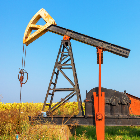 A Small private oil derrick pumps oil on the field. The old handicraft oil rig in the background of the creative industrial design.