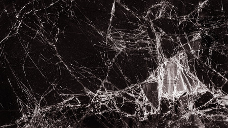 cracked glass: broken cracked glass with big hole over dark background