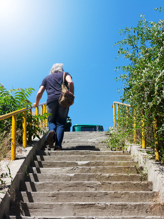 The gray-haired man climbs the concrete stairs in bright sunlight Stock Photo