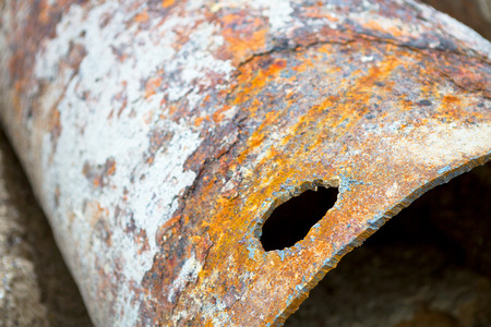 Fragments of old large water pipes. After many years of operation, corroded metal pipe destroyed. Rusty steel tube with holes metal corrosion. Selective focus. 스톡 콘텐츠