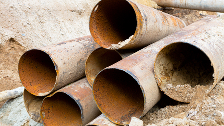 metal corrosion: Fragments of old large water pipes. After many years of operation, corroded metal pipe destroyed. Rusty steel tube with holes metal corrosion. Selective focus. Stock Photo