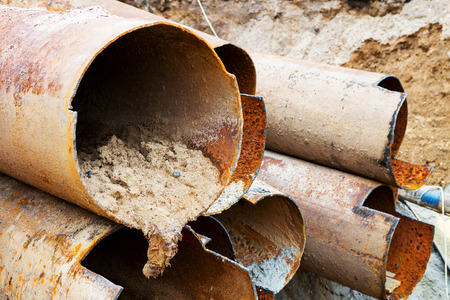 Fragments of old large water pipes. After many years of operation, corroded metal pipe destroyed. Rusty steel tube with holes metal corrosion. Selective focus. Stock Photo