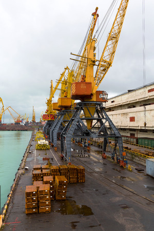 Odessa, Ukraine - October 13, 2016: Container cranes in cargo port terminal, cargo cranes without job in an empty harbor port. A crisis. Defaulted paralyzed entire economy Editorial