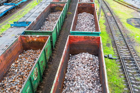 Odessa, Ukraine - October 13, 2016: Heavy industry - coal, metal, square iron pipe is transported in railway freight wagons of the train yard Stock Photo