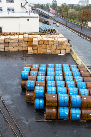 Odessa, Ukraine - October 13, 2016: Industrial products, raw materials, timber and sheet steel mill in the industrial port quay shopping ready for loading cargo seagoing vessels Editorial