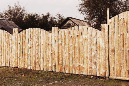 Rural landscape with a wooden fence around the old house Stock Photo