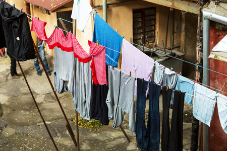 tearing down: Wash clothes hanging on a clothesline in a poor residential quarter of the city