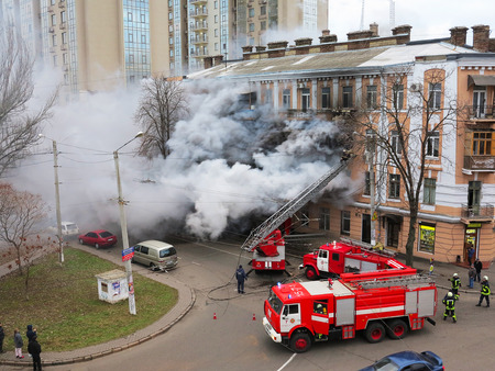 Odessa Ukraine - December 29, 2016: A fire in apartment building. Strong bright light and clubs smoke clouds window of their burning house. Firefighters extinguish fire in house. Work on fire stairs Editorial