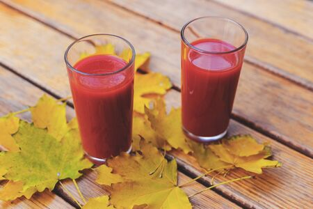 Tomato juice in a glass cup and yellow autumn leaves on a wooden table. Selective focus.