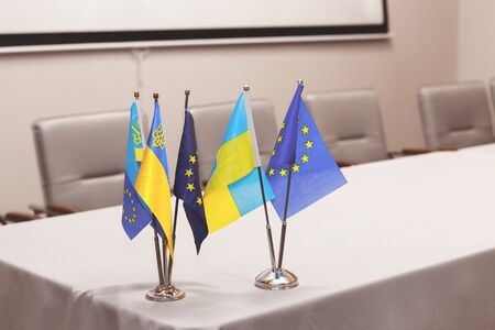 Small flags of the European Union and Ukraine on a white table, a conference hall in the background. Free space for text.