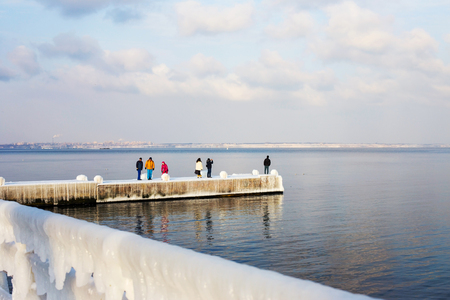 Odessa, Ukraine - January 10, 2017: People walk on the citys seaside promenade. Snow and ice. Icing after a strong winter storm with strong frosts. Editorial