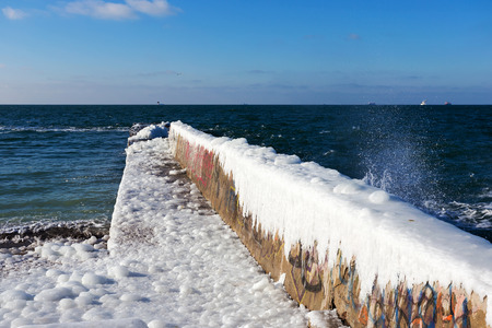 Snow and ice on the sea promenade. Icing seaside promenade after a strong winter storm with heavy frost.