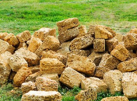 A pile of construction stone shell rock on a green lawn is scattered in disarray. Yellow building stone, mined in the catacombs.