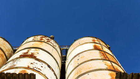 Old, abandoned concrete plant with iron rusty tanks and metal structures. The crisis, the fall of the economy, stop production capacity led to the collapse. Global catastrophe. Stock Photo