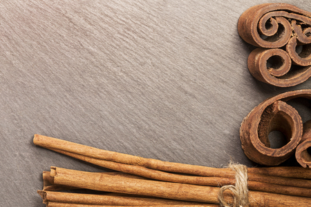 Cinnamon sticks on black background close up. Top view from above. Its suitable for background, backdrop, wallpaper including website decor and artwork design. Stock Photo