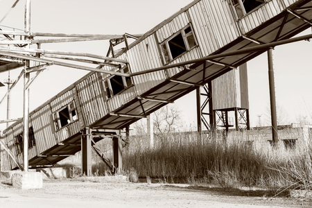Old, abandoned concrete plant with iron rusty tanks and metal structures. The crisis, the fall of the economy, stop production capacity led to the collapse. Global catastrophe. Old photo effect