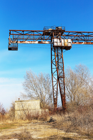 derrumbe: Old, rusty gantry crane on railroad, an abandoned concrete plant. Crisis, collapse of economy, and shutdown of production capacities have led to collapse. Global catastrophe. Effect of an old vintage photo. Foto de archivo