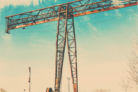 Old, rusty gantry crane on railroad, an abandoned concrete plant. Crisis, collapse of economy, and shutdown of production capacities have led to collapse. Global catastrophe. Effect of an old vintage photo. Stock Photo