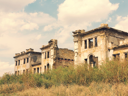 Ruins of an ancient castle Tereshchenko Grod in Zhitomir, Ukraine. In background blue sky, on earth grows green grass. Palace of 19th century. Vintage effect, scratches and cracks.