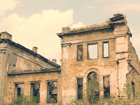 Ruins of an ancient house in Odessa, Ukraine. Historic building destroyed by vandals of the proletariat during revolution in 20th century. Vintage effect, scratches and cracks.