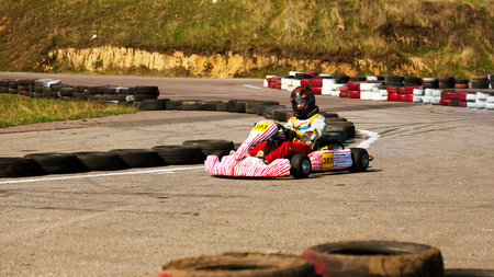 ODESSA, UKRAINE - APRIL 2, 2017: Competitions on the picture, pilots in helmet and in racing clothes participate in the card race. Carting show. Children and adult racers on bright branded maps. Editorial