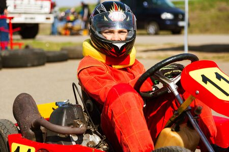 motorizado: ODESSA, UKRAINE - APRIL 2, 2017: Competitions on the picture, pilots in helmet and in racing clothes participate in the card race. Carting show. Children and adult racers on bright branded maps. Editorial