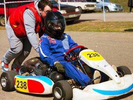 motorizado: ODESSA, Ucrania - 2 abril 2017 Las competiciones en la imagen, los pilotos en el casco y en las carreras de la ropa participar en la carrera de la tarjeta. Karts espectáculo. Los niños y los adultos en los corredores de mapas brillantes de marca. Editorial