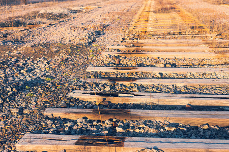 sleepers: Background, Rotting wooden sleepers, old railway in perspective. Crisis, devastation. Stock Photo