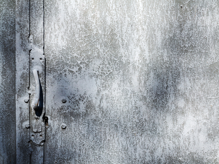 corroded: Creative metal background. An old metal door with a lock and a door handle. Flat background texture of dirty metal. As the main background for vintage design