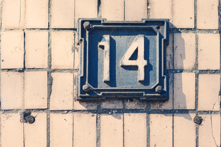 four objects: Retro metal plate with drawings 14 on a white brick wall, old house, house number index. Suitable as a background for any your project.