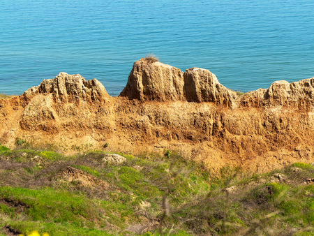 Deep sandy cliff on the background of blue sky. The destruction of the coast as a consequence of soil erosion. Landslide - threat to life. Stock Photo