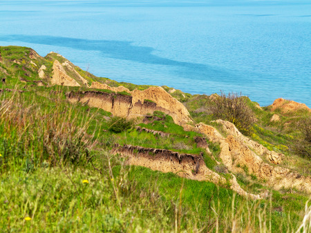 soil erosion: Deep sandy cliff on the background of blue sky. The destruction of the coast as a consequence of soil erosion. Landslide - threat to life. Stock Photo