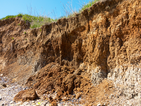 suelo arenoso: Deep sandy cliff on the background of blue sky. The destruction of the coast as a consequence of soil erosion. Landslide - threat to life. Foto de archivo