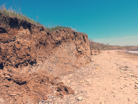 Deep sandy cliff on the background of blue sky. The destruction of the coast as a consequence of soil erosion. Landslide - threat to life.