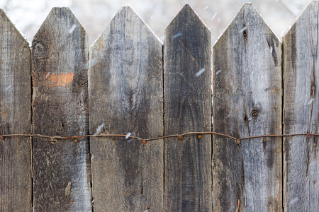Wooden fence in the winter. Snow in motion. Old wooden boards, perfect background for your concept or project.