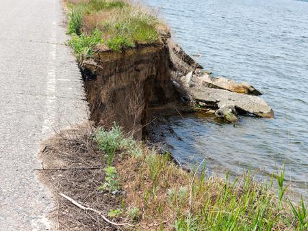 suelo arenoso: Profundo acantilado de arena en el fondo de cielo azul. La destrucción de la costa como consecuencia de la erosión del suelo. Deslizamiento - amenaza a la vida.