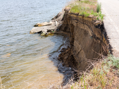 Deep sandy cliff on the background of blue sky. The destruction of the coast as a consequence of soil erosion. Landslide - threat to life. 版權商用圖片