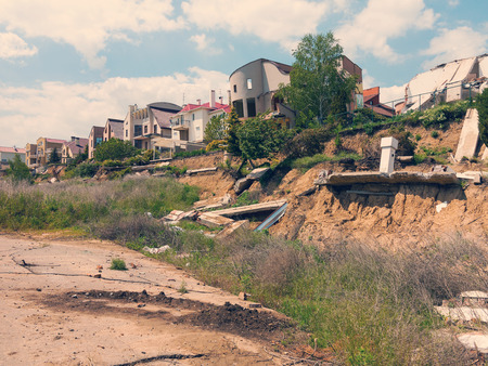 dirty room: landslide caused by torrential rains of hurricane CHRISTIE. Broken road asphalt cracked, and came down with landslide. Destroyed residential buildings of cottage town elite settlement. earthquake