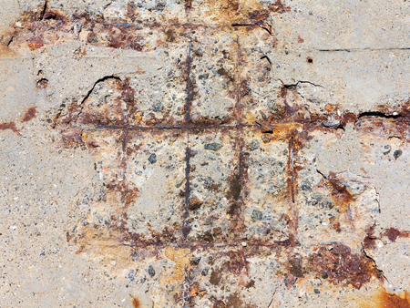 Reinforced concrete surface is covered with cracks, scratches, inclusions of granite and rusty metal bars. You can use as the background for any of your project. Foto de archivo