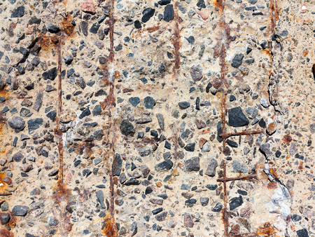inclusions: Reinforced concrete surface is covered with cracks, scratches, inclusions of granite and rusty metal bars. You can use as the background for any of your project. Stock Photo