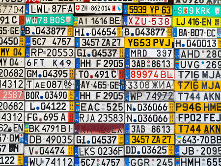 Odessa, Ukraine - circa 2017: License numbers auto from all over the world on display. Discontinued license plate of cars from Europe car on the old wall. Background of old vintage antique car license plates of Europe.