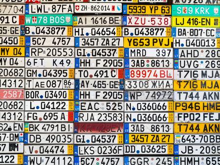 Odessa, Oekraïne - circa 2017: licentienummers auto van over de hele wereld te zien. Beëindigde nummerplaat van auto's van de auto van Europa op de oude muur. Achtergrond van de oude uitstekende kentekenplaten van de oldtimer van Europa.