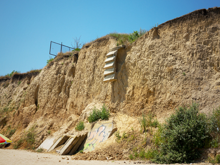 soil erosion: ?oncrete staircase collapsed in a landslide of soil after heavy rains on the coast of the Black sea. Destruction of the coast as a consequence of soil erosion. Landslide - threat to life.