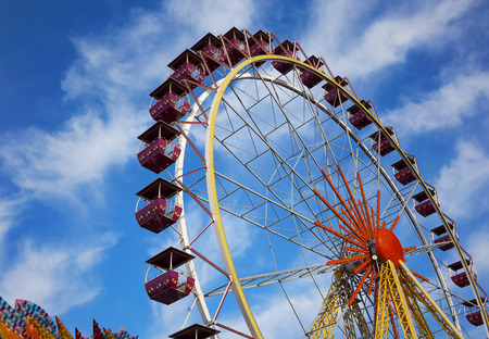 Ferris wheel. Open booths of the Ferris wheel at the sky with beautiful clouds. Rides at city Park. Stock Photo