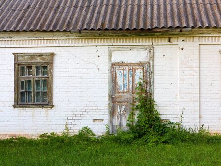 Old barn white brick under the open sky in village. Wooden door with iron bolts and lock is overgrown with climbing plants.  Rural landscape in summer in Sunny clear day.