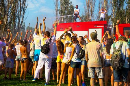 ODESSA, UCRANIA - el 5 de agosto de 2017: Los muchachos y las muchachas en ropa mojada se divierten para hacer selfie durante el festival de Holi. El bombero sonriente que se sienta en el carro de bomberos vierte el agua en la gente de brandsby. Festival de pinturas de colores, colores, amor. Fiesta de color Foto de archivo - 83902078