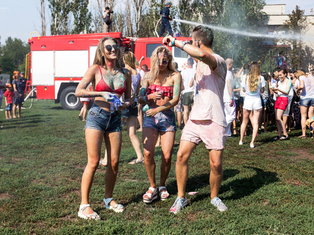 dirty: ODESSA, UKRAINE - August 5, 2017: Boys and girls in wet clothes fun to do selfie during festival of Holi. Smiling fireman sitting on fire truck pours water on people from brandsby. Festival Color fest