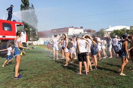 Odessa, Oekraïne - 5 augustus 2017: jongens en meisjes in natte kleding plezier om selfie te doen tijdens festival van Holi. De glimlachende brandweermanzitting op brandvrachtwagen giet water op mensen van brandsby. Festival Color fest Redactioneel