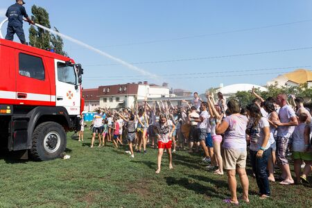 dirty: ODESSA, UKRAINE - August 5, 2017: Boys and girls in wet clothes fun to do selfie during festival of Holi. Smiling fireman sitting on fire truck pours water on people from a hose. Color fest